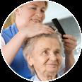Nurse combing the hair of a senior woman